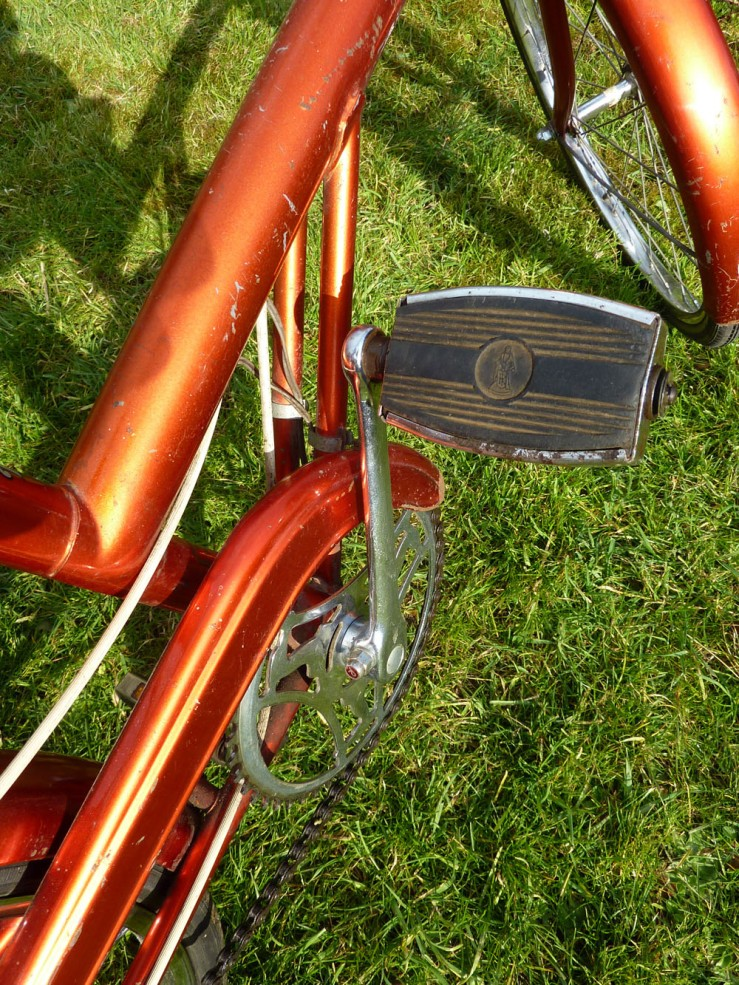 This view shows, among other things, the twin bracing stays formed by extending the chain stays around the bottom bracket and up to the main beam. You can also see the Raleigh pedal, complete with logo moulded into the heavy solid rubber body.