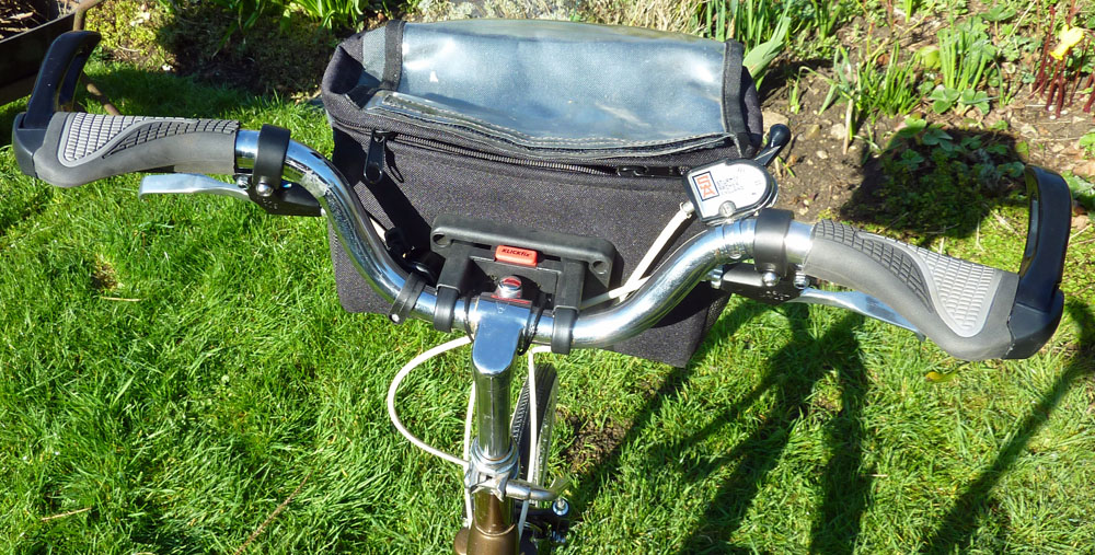 A rider's-eye view of the handlebar cluster, showing the Klickfix bracket, the Sturmey-Archer 3-speed trigger and a bell, tcuked away by the bag bracket. This set-up enables the bike to be stood upside for maintenance, supported well by the handlebar grip extensions and saddle.